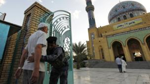 A man is frisked before being allowed to enter a Sunni mosque for prayers.