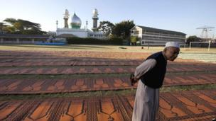 A mosque attendant in Nairobi, Kenya waits for Muslims to arrive for prayers to mark the end of the Eid festival