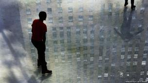 A building is reflected on the ice of the ice rink at Rockefeller Center in New York