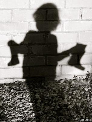 Shadow of child holding boots