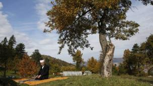 An elderly Bosnian Muslim prays outdoors in the outskirts of Sarajevo on 15 October 2013