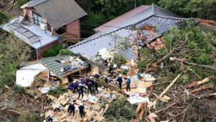 Rescue workers look for survivors as they stand on the rubble of a house buried by mudslides after a powerful typhoon hit Izu Oshima island on 16 October 2013