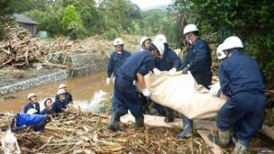 Rescue workers recover the body of a victim from a site that was damaged by a landslide caused by Typhoon Wipha in Izu Oshima island, south of Tokyo, in this photo taken by Kyodo, 16 October 2013