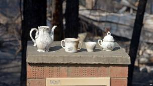 Saved crockery sits on the letterbox at the front of a house destroyed by bushfires in Winmalee in Sydney's Blue Mountains on 18 October 2013
