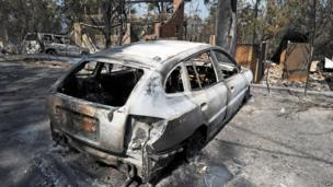 A burnt-out car sits in front of a house destroyed by bushfires in Winmalee in Sydney's Blue Mountains on 18 October 2013