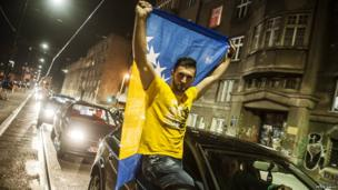 Man sitting in open window of car in traffic holds up Bosnian flag. Photo: Peter Kallo