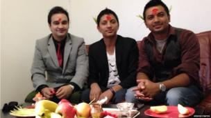 Men wearing traditional Nepalese headpieces sit in front selection of fruit. of Photo: Kishor Panthi