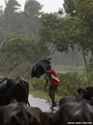 A boy tries to cover himself with an umbrella during heavy rain brought by Cyclone Phailin in the southern Indian state of Andhra Pradesh