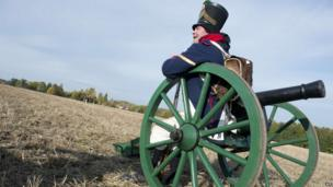 Re-enactor dressed as French soldier sits on artillery piece, Leipzig (20 October)