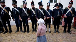 Girl in period costume looks at re-enactors dressed as French soldiers, re-enactment of the Battle of the Nations, Leipzig (20 October)