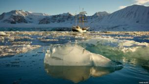 Tall ship next to sections of glacier in the Arctic Circle