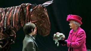 The Queen receives flowers from a child actor as she inspects the horse puppet from the play War Horse, during a visit with Prince Philip to London's National Theatre to commemorate its 50th anniversary.