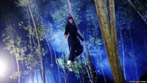 A stuntman flies through the forest on a wire during the production of Ciung Winara