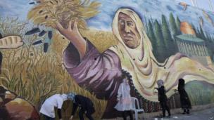 Palestinian artists paint a mural symbolising resistance and the right of the return of Palestinian refugees, in the West Bank city of Nablus, on 24 October 2013