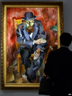 A man looks at Man in a Bowler Hat by Robert Falk, on display ahead of a Sotheby's auction in Moscow, on 24 October 2013