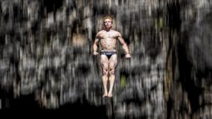Alain Kohl of Luxembourg dives from the 27 metre platform at Maya Bay in the Andaman Sea during the final stop of the 2013 Red Bull Cliff Diving World Series.