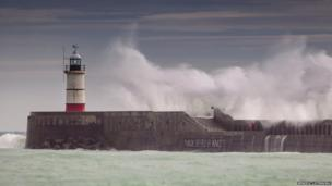Sea wall and lighthouse at Newhaven, East Sussex battered by waves. Photo: Benedict Stenning