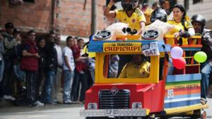 Participants descend a hill in a homemade Chiva during the XXIV Car Festival in Medellin, Colombia, on 27 October 2013.