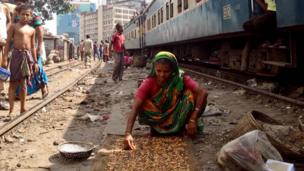 A women prepares food on near the train line in Dkaka.