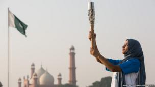 The Queen's Baton is held aloft by Pakistani karate athlete Benish Akbar, with the Badshahi Mosque in the background, in Lahore, Pakistan.