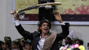 A groom wearing traditional Yemeni costume holds up a sword during a mass wedding ceremony in Sanaa