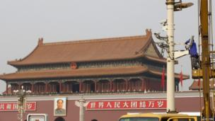 A man works on a security camera installed at Tiananmen Square in Beijing