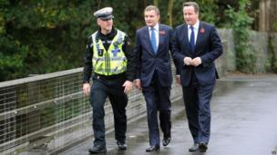 Prime Minister David Cameron speaks with Traffic Police Inspector Rob Gwynne-Thomas and Secretary of State for Wales David Jones overlooking the M4 outside Cardiff.