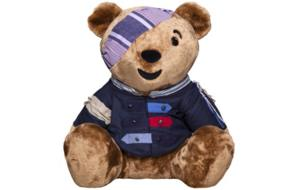Bear with a blue shirt with patches and buttons and a purple striped bandana.