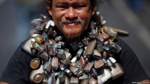 A protester wears a chain with many amulets as he joins others in a march towards central Bangkok.