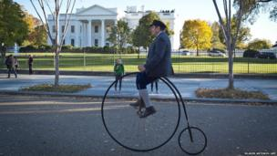 A member of the Dandies and Quaintrelles social group rides his penny farthing bicycle in front of the White House