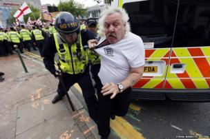 A man is moved by police during clashes at a march by the English Defence League in Birmingham