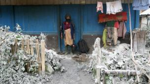 A woman stands outside her house as her front yard is covered with volcanic ash from the eruption of Mount Sinabung, in Mardingding, North Sumatra, Indonesia