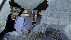 A Chinese police officer is framed by the glass window of a vehicle damaged by explosions outside the provincial headquarters of ruling Communist Party in Taiyuan in Shanxi province, 6 November 2013