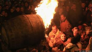 A burning barrel soaked in tar is carried through the crowds at the annual Ottery St Mary Tar Barrel festival