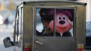 A woman rides a motorcycle taxi with a Disney character Minnie Mouse balloon in Beijing