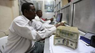 "An employee serves customers at a Dahabshiil bureau in Somalia""s capital Mogadishu, on 7 November 2013"