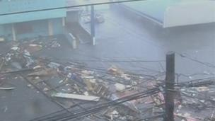 Debris float on a flooded road as strong winds and rain continue to batter buildings after Typhoon Haiyan hit Tacloban city, Leyte province, the Philippines, in this still image from video 8 November 2013