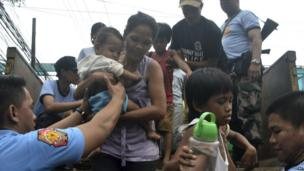 Residents living near the slopes of Mayon volcano are evacuated to public schools by police in anticipation of the powerful typhoon Haiyan, 7 November 2013