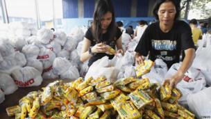 Volunteers pack relief goods in government warehouse