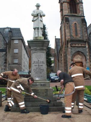 Fire crew clean a war memorial