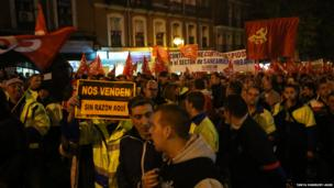 Hundreds of men with flags and banners protest in the street. Photo: Tanya Hanbury-Aggs