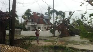 Man carries child near roofless house. Photo: Darren White