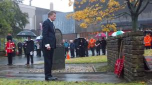 """Secretary of State for Wales David Jones lays a wreath at the Royal Mint""""s war memorial in Llantrisant, Wales."""
