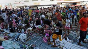 Residents watch as others grab looted goods thrown out from the second floor of a warehouse in the town of Guiuan, Eastern Samar province, in the central Philippines on 11 November 2013, days after Super Typhoon Haiyan devastated the town
