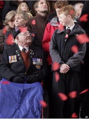 World War II veteran from Liverpool, England, Alan Rowe, left, looks up at a young boy as paper poppies fall during an Armistice Day ceremony under the Menin Gate in Ypres, Belgium