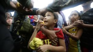 A Philippine air force officer hands out orange slices to typhoon survivors as they line up to board a C-130 military transport plane in Tacloban city, central Philippines