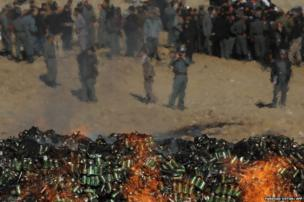 Afghan government officials and policemen watch as a cache of alcohol and drugs burn in Kabul
