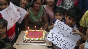 Indian cricket fans of Sachin Tendulkar hold placards and gather to cut a cake in his honour in Hyderabad, India, Wednesday, Nov. 13, 2013