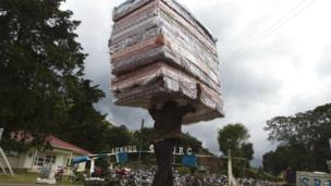 A man carries mattresses over to the Democratic Republic of Congo at the Bunagana border crossing with Uganda (9 November 2013)