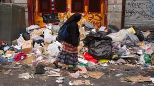 A woman walks past bins overflowing with rubbish in the city centre of Madrid